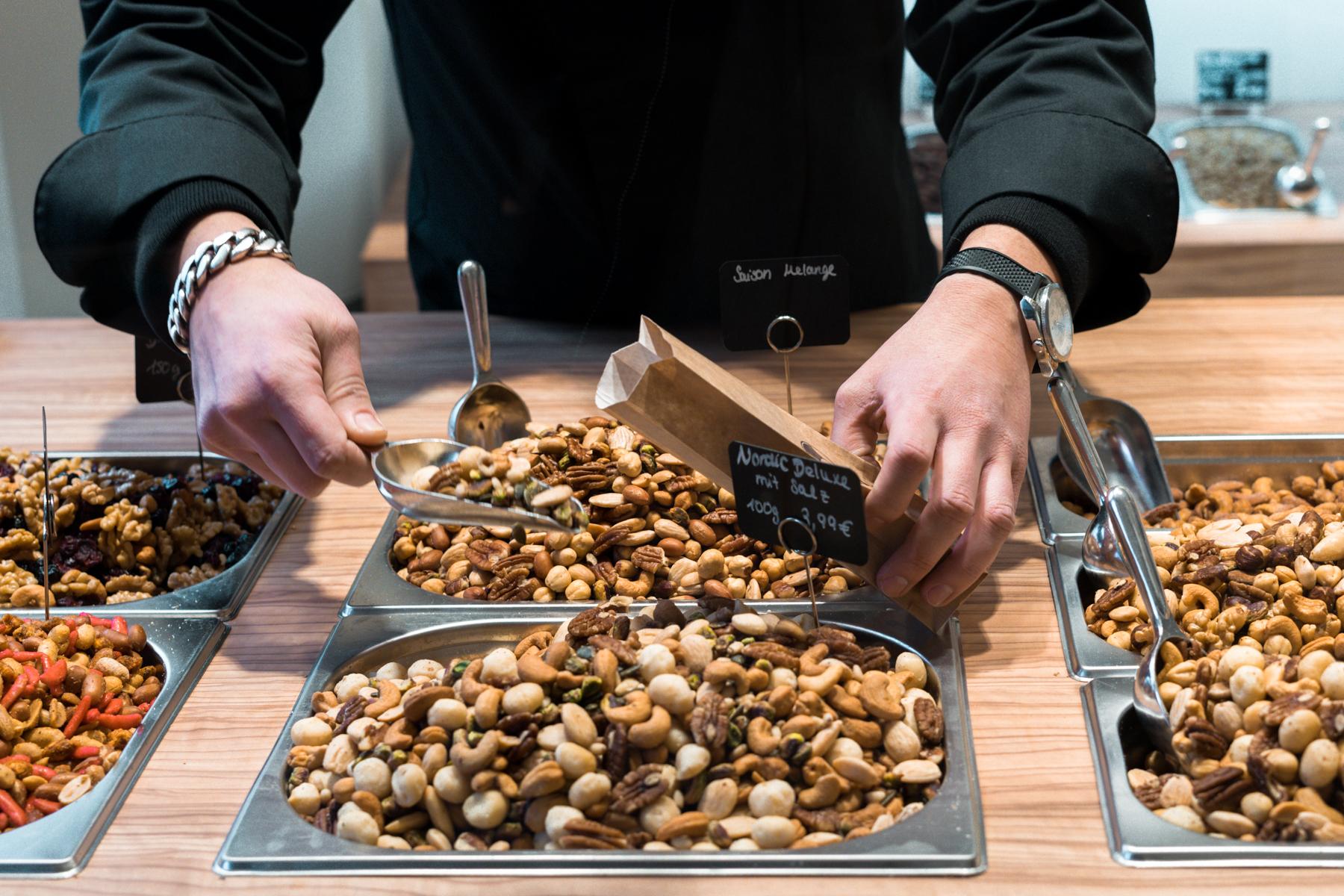 Mitarbeiter füllt Nüsse in eine Tüte.