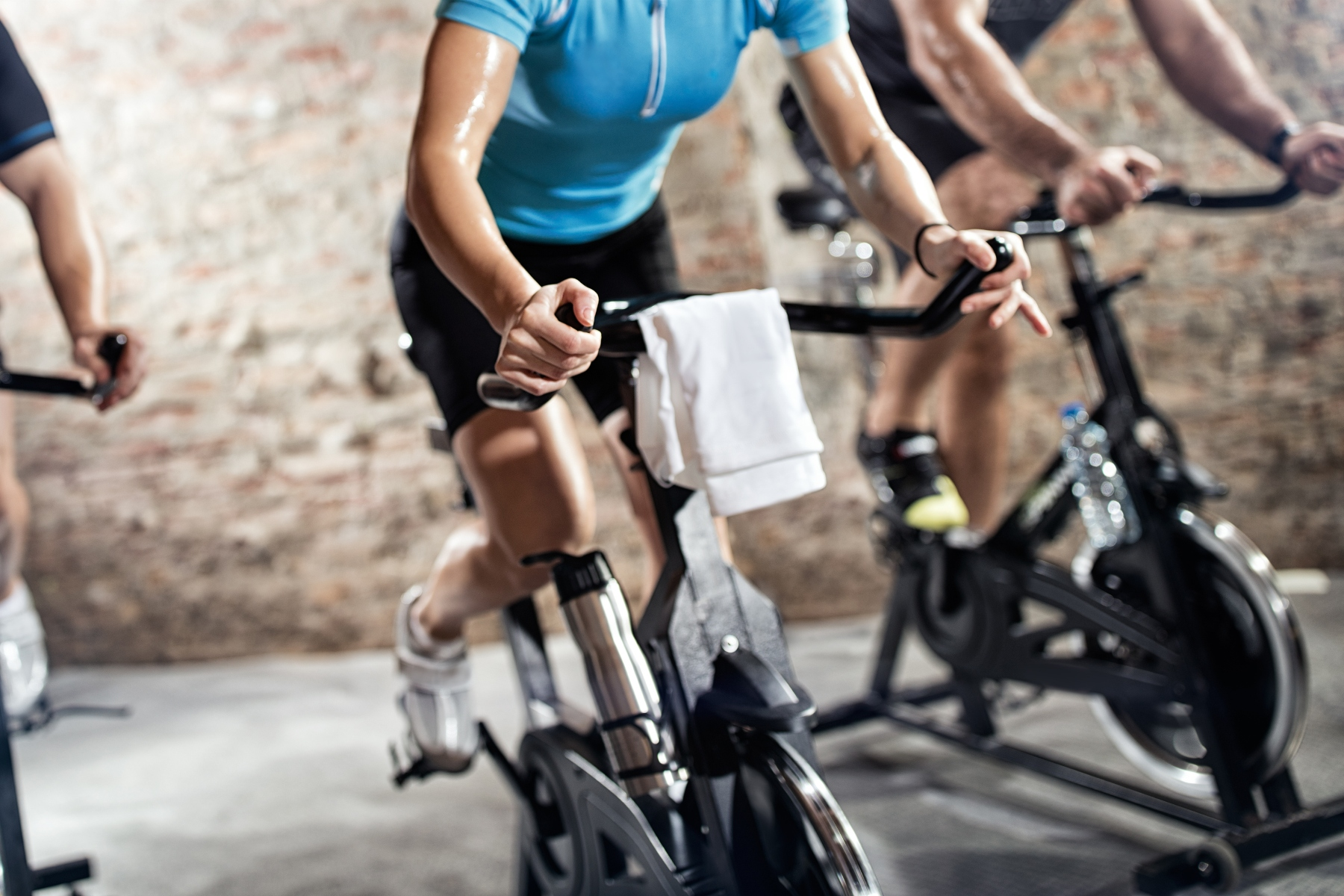 sports clothing people riding exercise bikes, cardio fitness class – ©AdobeStock