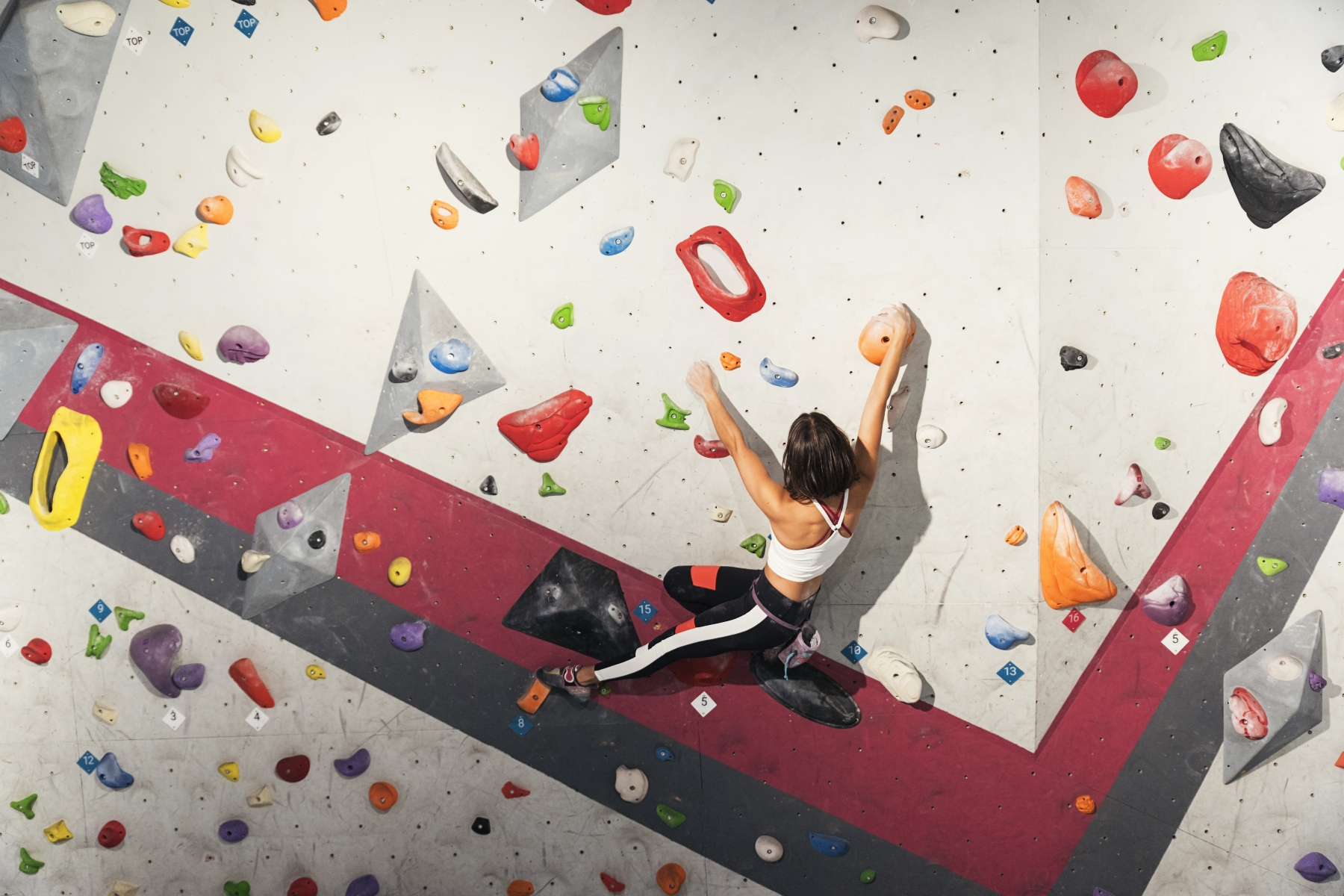 Woman practicing rock climbing on artificial wall indoors. Active lifestyle and bouldering concept. – ©AdobeStock