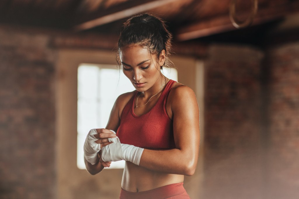 Female boxer wearing strap on wrist. Fitness young woman with muscular body preparing for boxing training at gym. – ©AdobeStock