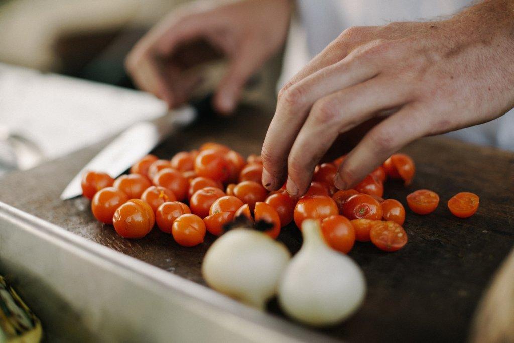 Mann, der Tomaten schneidet.