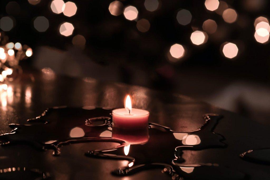 Kerze auf einem Tisch in dunklem Licht